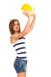 Beautiful young woman throwing a beach ball. Royalty Free Stock Photos