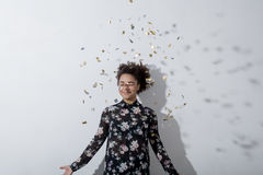 Beautiful young woman throwing confetti. And looking happy indoors stock photo