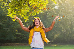 Beautiful young woman throwing leaves Stock Photos