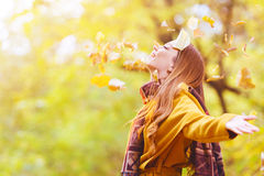Beautiful young woman throwing leaves in a park Stock Photos