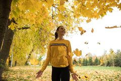 Beautiful young woman throwing yellow leaves in a park, enjoying. Telephoto shot royalty free stock images