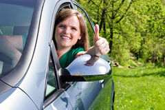 Beautiful young woman with thumbs up in her new car Royalty Free Stock Photos