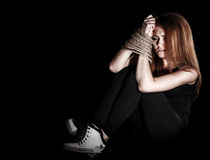 Beautiful young woman with tied arms sitting on the floor Stock Photography