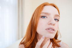Beautiful young woman touching and considering her face Stock Photo