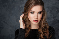 Beautiful young woman touching her curly long hair Royalty Free Stock Image