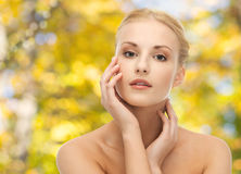 Beautiful young woman touching her face. Beauty, people and body care concept - beautiful young woman touching her face over yellow autumn background Royalty Free Stock Photo