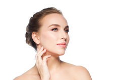 Beautiful young woman touching her face. Beauty, people and health concept - beautiful young woman touching her face and neck over white background Stock Photography