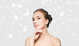 Beautiful young woman touching her face over snow. Beauty, people, winter and health concept - beautiful young woman touching her face over gray background and Stock Photography