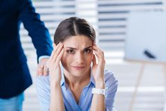 Beautiful young woman touching her head while feeling unwell. Headache. Young tired upset women touching her head while being at work and having a terrible Royalty Free Stock Image