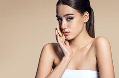 Beautiful young woman touching her perfect skin face, professional make-up Stock Image