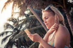 Beautiful young woman tourist in bikini on beach looking smartphone during beach holidays stock photography