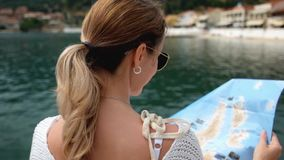 Beautiful Young Woman with tourist map. At a bay stock footage