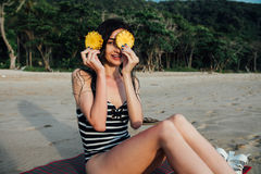 Beautiful young woman tourist In a striped swimsuit holding two ripe pineapple against her eyes. Stock Image