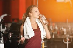 Beautiful young woman with towel and bottle of water