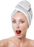 Beautiful young woman in towel, with a cherry berry Royalty Free Stock Photos