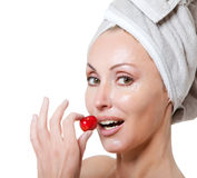 Beautiful young woman in towel, with a cherry berry Stock Image