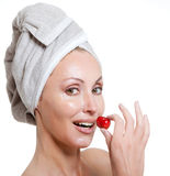 Beautiful young woman in towel, with a cherry berry Royalty Free Stock Images