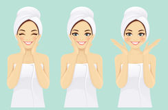 Beautiful young woman in towel. With clean fresh skin touch own face Stock Photos
