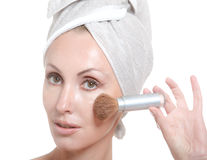 Beautiful young woman in towel with a cosmetic brush Stock Photo