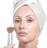 Beautiful young woman in towel with a cosmetic brush Stock Image