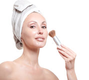 Beautiful young woman in towel with a cosmetic brush Stock Images
