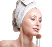 Beautiful young woman in towel with a cosmetic brush Royalty Free Stock Photo