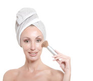 Beautiful young woman in towel with a cosmetic brush Royalty Free Stock Photography