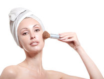 Beautiful young woman in towel with a cosmetic brush Royalty Free Stock Photos