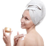 Beautiful young woman in towel with a cosmetic cream Stock Photos