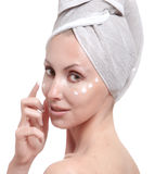 Beautiful young woman in towel with a cosmetic cream Royalty Free Stock Photo
