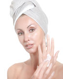 Beautiful young woman in towel with a cosmetic cream Royalty Free Stock Photography