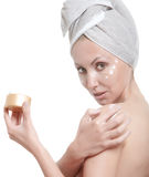 beautiful young woman in towel with a cosmetic cream Royalty Free Stock Photos