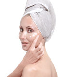 Beautiful young woman in towel with a cosmetic cream Royalty Free Stock Images