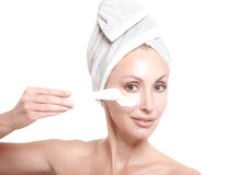 Beautiful young woman in towel with a cosmetic cream Stock Photo