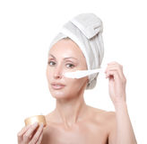 Beautiful young woman in towel with a cosmetic cream Royalty Free Stock Image