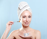Beautiful young woman in towel with a cosmetic cream Stock Photography