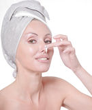 The beautiful woman in towel with a cosmetic cream.Portrait on a white background Royalty Free Stock Photo