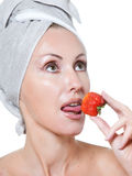 Beautiful young woman in towel with a strawberry Royalty Free Stock Image