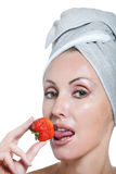 Beautiful young woman in towel with a strawberry Stock Photo