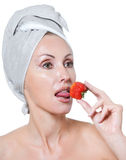 Beautiful young woman in towel with a strawberry Royalty Free Stock Images