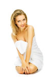 Beautiful young woman in towel terry sits Stock Photography