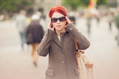 Beautiful young woman in the town with sunglasses and handbag, purse stock photo