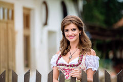 Beautiful young woman in traditional bavarian dress in park Royalty Free Stock Image
