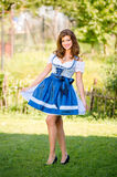 Beautiful young woman in traditional bavarian dress in park Stock Photos