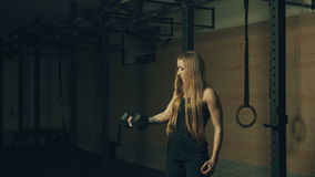 Beautiful young woman training with dumbbells in gym stock video footage