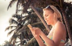 Beautiful young woman traveler in bikini on beach texting smartphone during beach holidays royalty free stock photo
