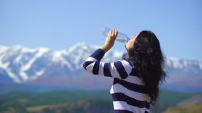 Beautiful young woman traveler drinks water on a background of beautiful mountains. 4k Woman relaxes on the top of the stock footage
