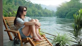 Beautiful young woman traveler resting in the mountains near the river.  stock footage