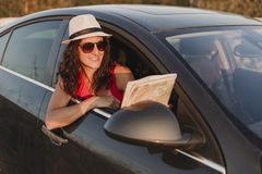 Beautiful young woman traveling in a car and holding a map. Travel and fun concept. Sunset and lifestyle.  royalty free stock image