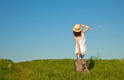 Beautiful young woman travelling with a suitcase. Rear view Stock Images